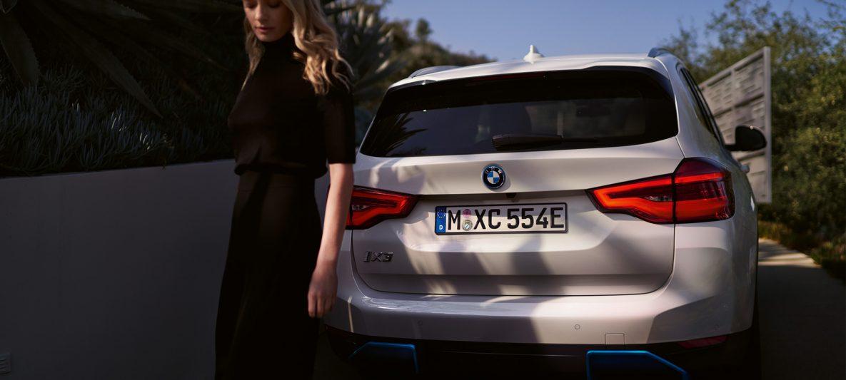 Heck mit BMW i spezifischem Diffusor BMW iX3 G08 2020 Mineralweiß metallic Heckansicht mit Frau